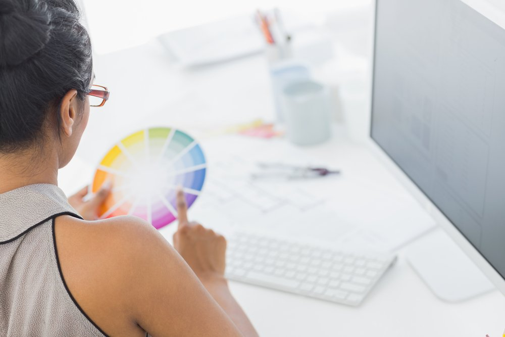 Designer working at her desk holding color wheel